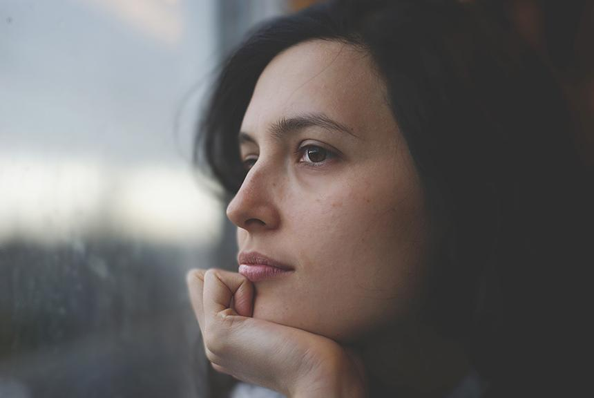 A thinking woman looking out of a window