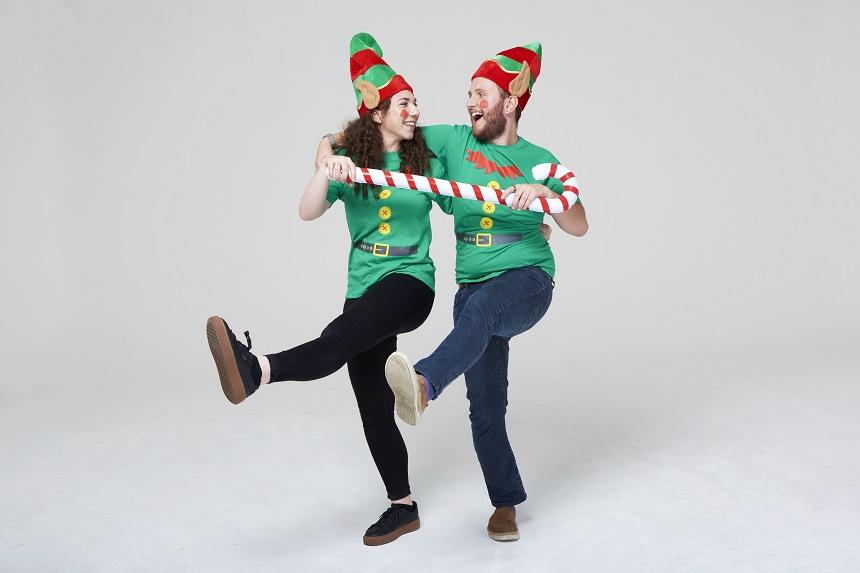 Two elves dancing with giant candy cane