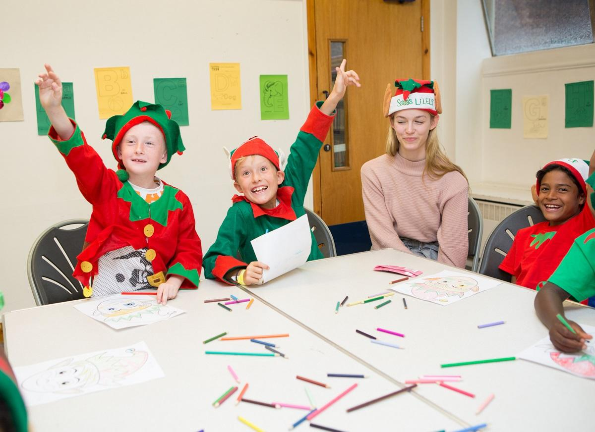 Three children dressed as Elves for Elf Day with their school teacher