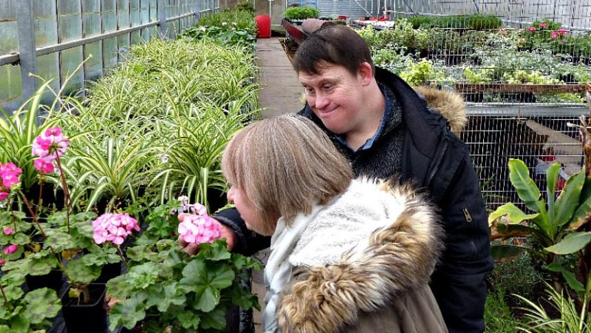 Couple with Down's syndrome smelling flowers