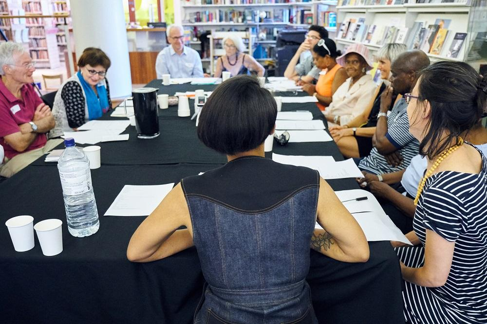 A group of people sat around a large table for the poetry workshop