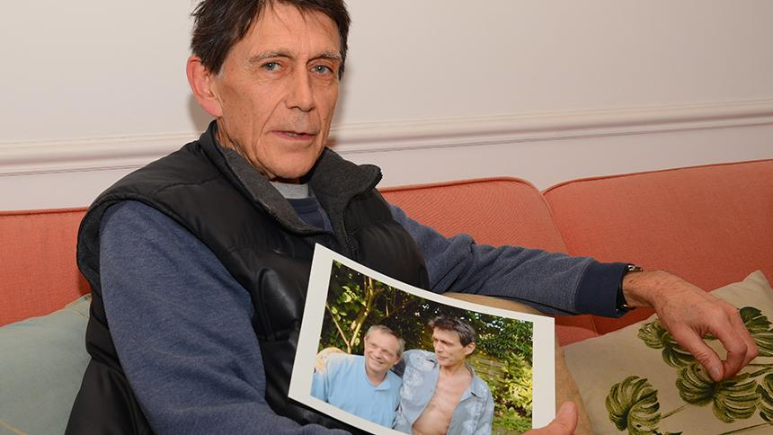 Nicky Stephens holding a photo of his late husband Carlo