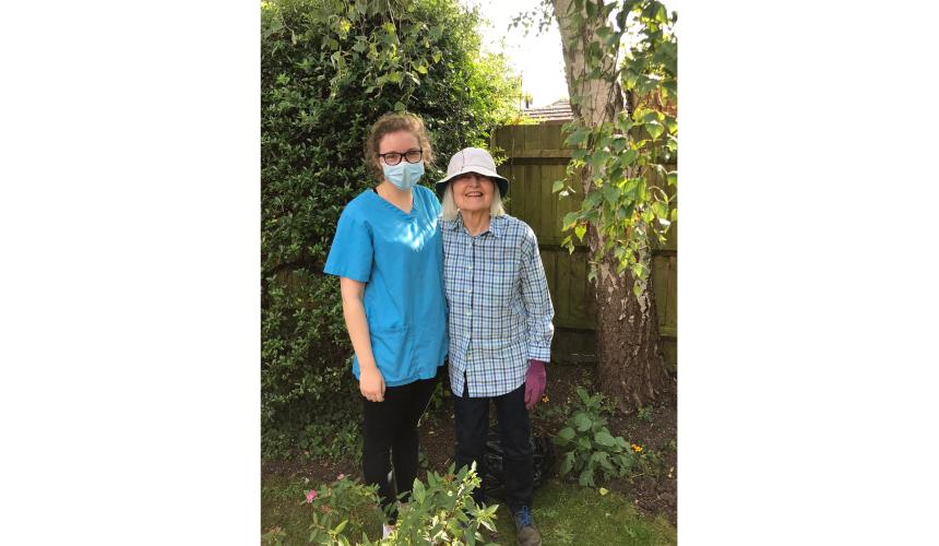 Ellie, a care home worker, wearing a mask and standing beside a resident