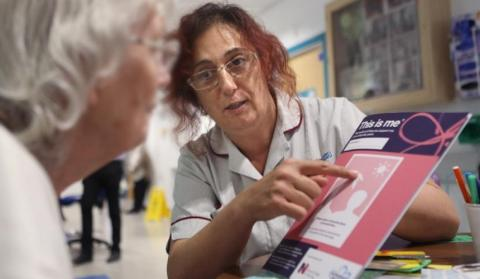 Nurse shows a hospital patient 'This is Me' publication