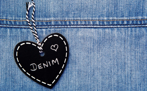 Black heart hanging on denim jeans with the word Denim written