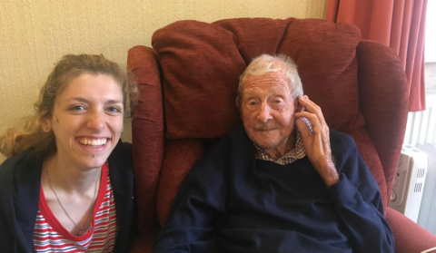 Ruby smiling beside her granddad, George, who is sitting in a red armchair