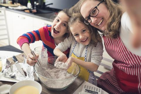 A woman baking cupcakes with kids