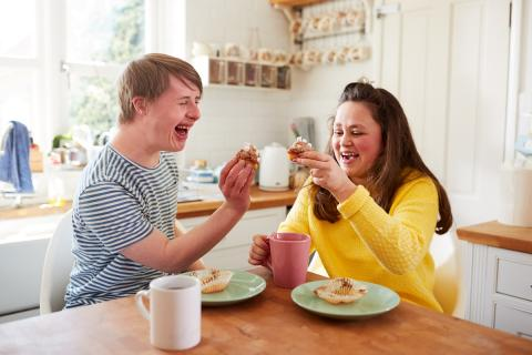 Two people laughing and enjoying cupcakes