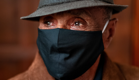 An older man from a minority background wearing a black facemask and a hat