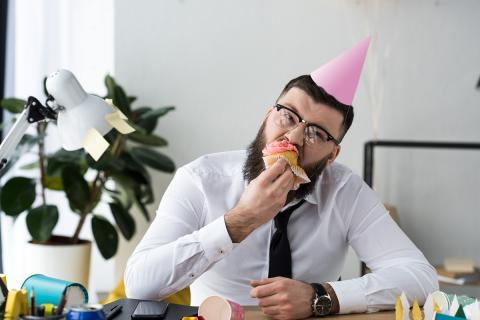 A man in a party hay eating cake at his desk
